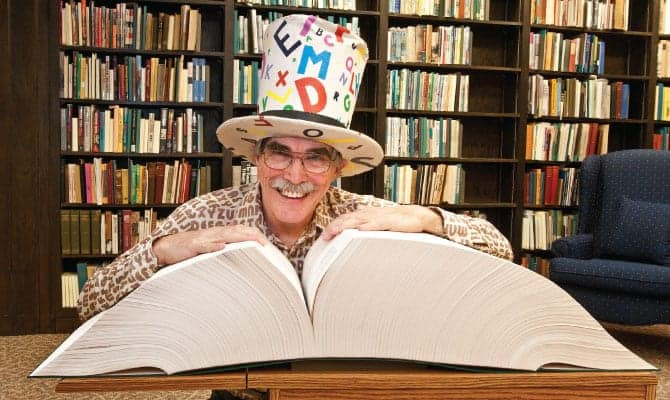 Man with crazy letter tophat smiling reading a book