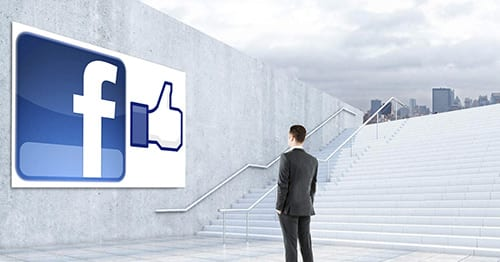 man standing on stairs looking at a facebook logo and like button